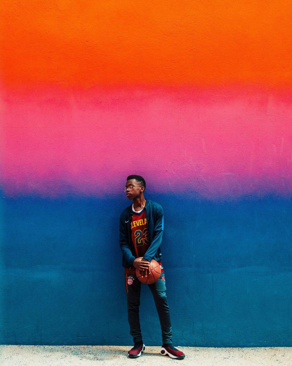 jongen met basketbal tegen gekleurde muur