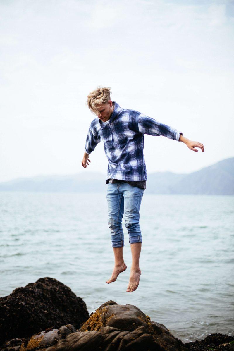 springende jongen op rots